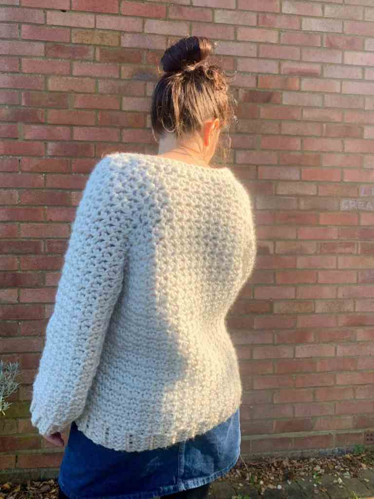 A woman wearing a cream chunky crochet cardigan and a denunciation skirt stands in front of a brick wall, her back is to the camera and her fingers just peek out the end of a sleeve