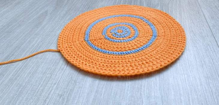 A side view of a crochet pi circle swatch, the increase rounds shown in blue