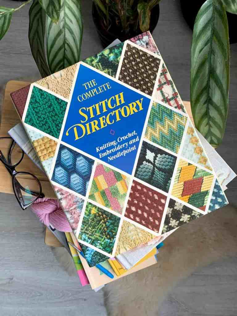 A copy of the complete stitch directory is on top of a pile of other crochet books