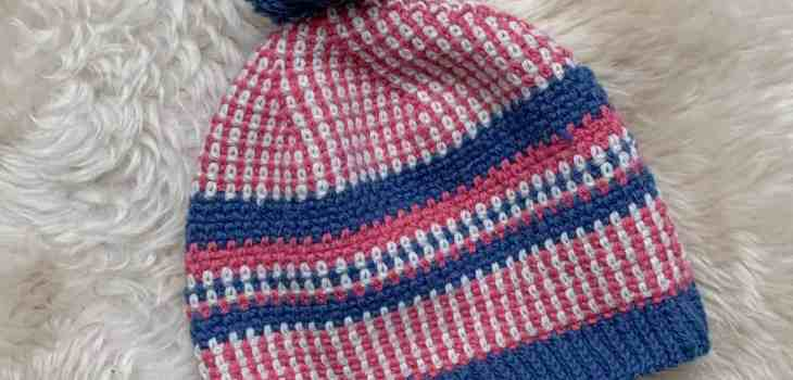 The scandi stashbuster crochet beanie hat pattern is laid at an angle on a sheepskin pelt