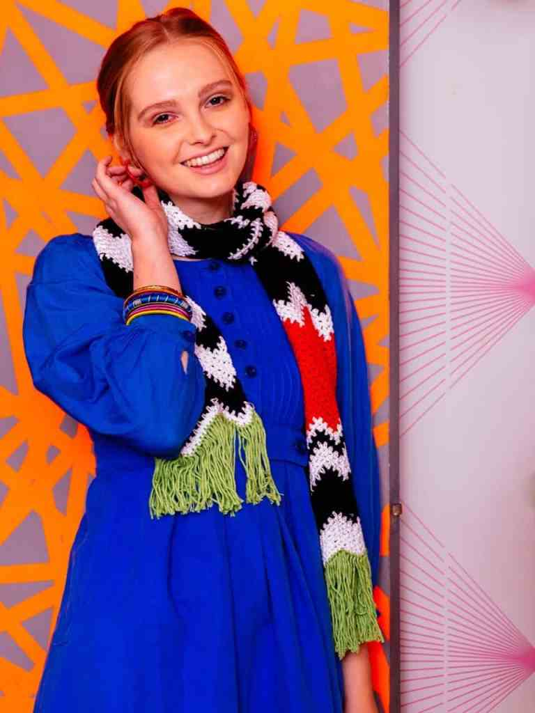 A woman smiles at the camera wearing a blue dress and a black white and orange striped shaft with green fringing