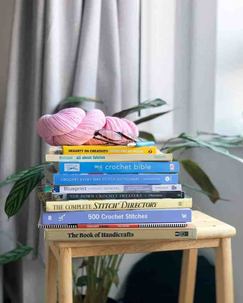 A stack of 10 crochet, yarn and creativity related books are resting on a wooden stool. A hank of pink wool, a pair of glasses and a crochet hook are on the top