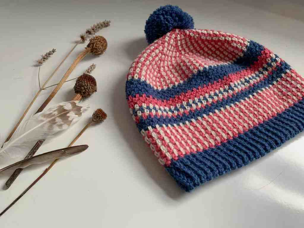 The folk style scandi stashbuster beanie crochet hat lays on a white surface paired with dried thistles, lavender and feathers