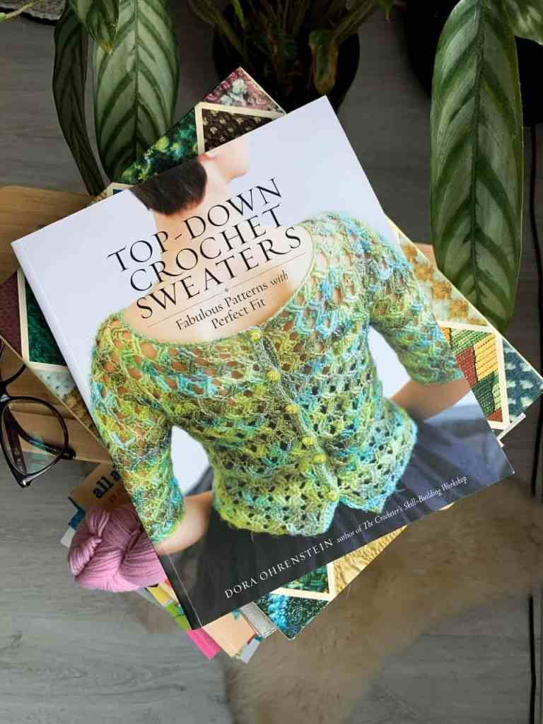 A copy of a book titled top-down crochet sweaters sits on top of a pile of crochet books
