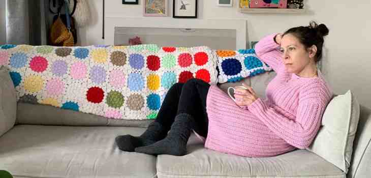 Dora sits on her sofa wearing a pink version of the winter solsitice crochet dress. She holds a cup of tea on her lap and looks out the window
