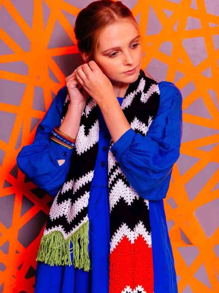 A woman fastens her earring while modelling a black and white chevron striped scarf which has an orange pop of colour with green fringe