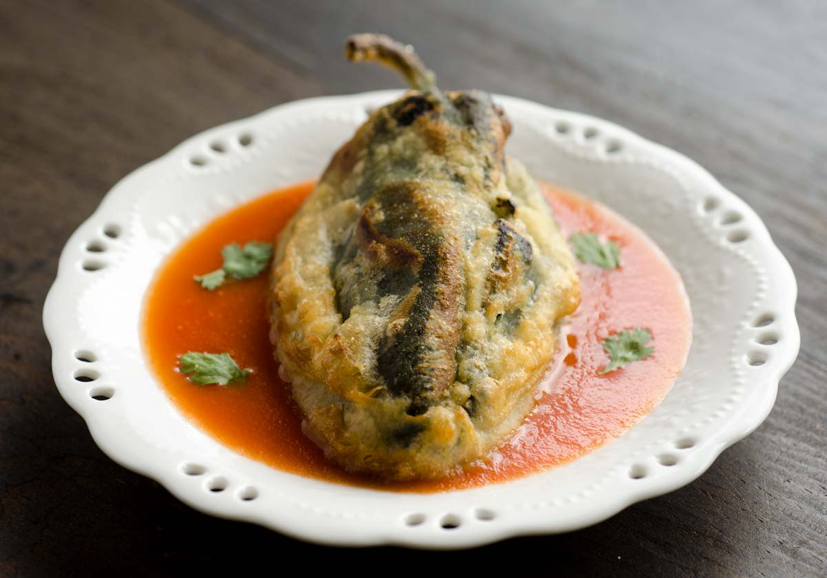 This recipe for vegan chiles rellenos is truly fantastic! They are crispy, melty, spicy and served on a garlicky tomato sauce.