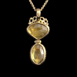 two yellow sapphires set in a hinged pendant