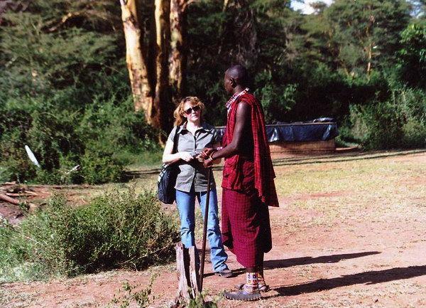 Regisseurin Gabriele Neudecker im Vorgespräch mit einem jugendlichen  Masai-Krieger, der praktische Sandalen im Busch trägt: abgeschnittene Motorradreifen.