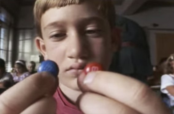 Actor Julius Rottwinkle, played by a youthful Leor Hackel of psychology, contemplates eating the two M&Ms in class that will result in him being thrown out of the classroom window by school principal Miss Trunchbull in the children's movie <em>Matilda</em>.  (Photo: MATILDA © 1996 TriStar Pictures, Inc. All Rights Reserved. Courtesy of TriStar Pictures.)