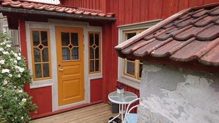 Halvfransk ytterdörr med ljusinsläpp med äkta spröjs 1:1 med romb i krysset. Fönster med äkta spröjs 2:1 med romb i övre krysset. Spröjsen linjerar mellan dörren och fönstren. Romberna har försetts med ett munblåst rött signalglas.