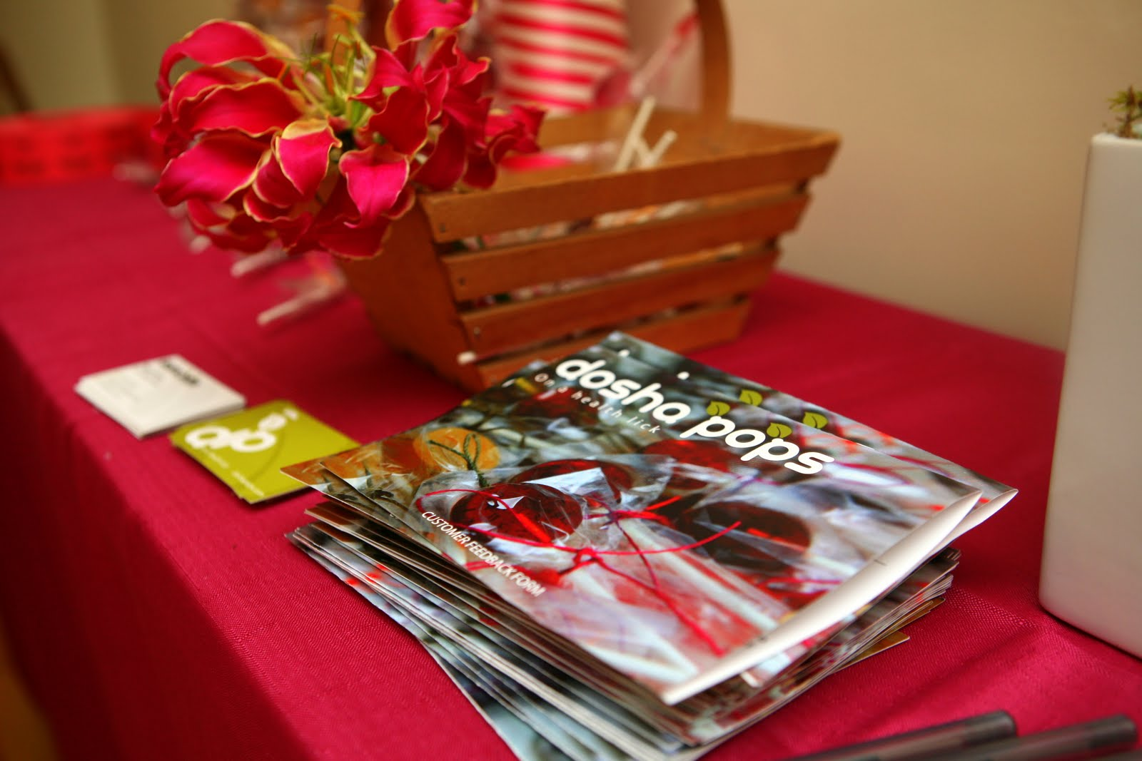 Dosha Pops brochure, basket and business cards on event table