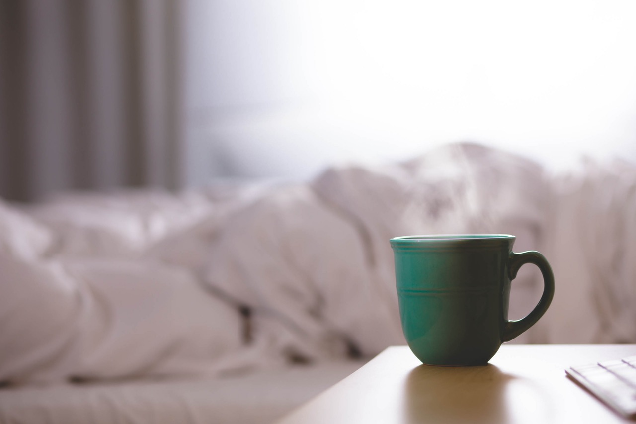Coffee cup on night table next to a white duvet covered bed