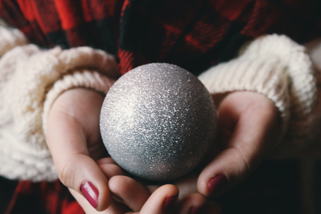Woman in flanel shirt holding a silver tree ornament