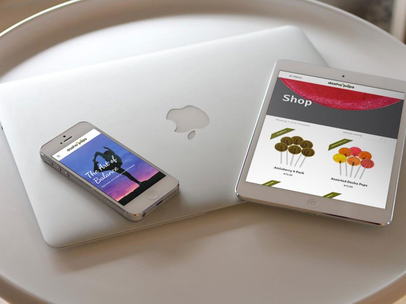 Laptop, mobile phone and tablet on a table showing the new Dosha Pops' website design