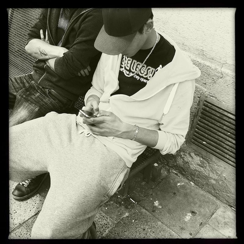 Jugendlicher mit Handy wartet auf den Bus