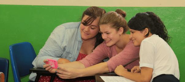 Schülerinnen fotografieren sich mit einem Handy