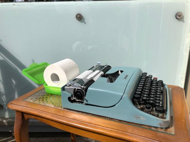 alte Schreibmaschine mit einer Rolle Toilettenpapier, eingespannt in den Wagen