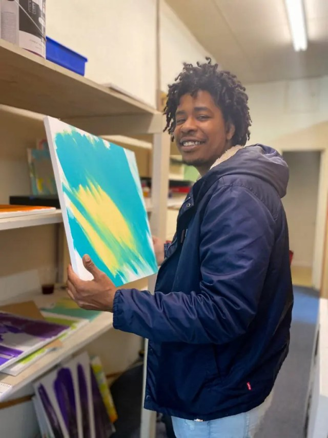 DoubleBlind: Transgender Rapper and Military Vet holds his psychedelic painting in a studio.