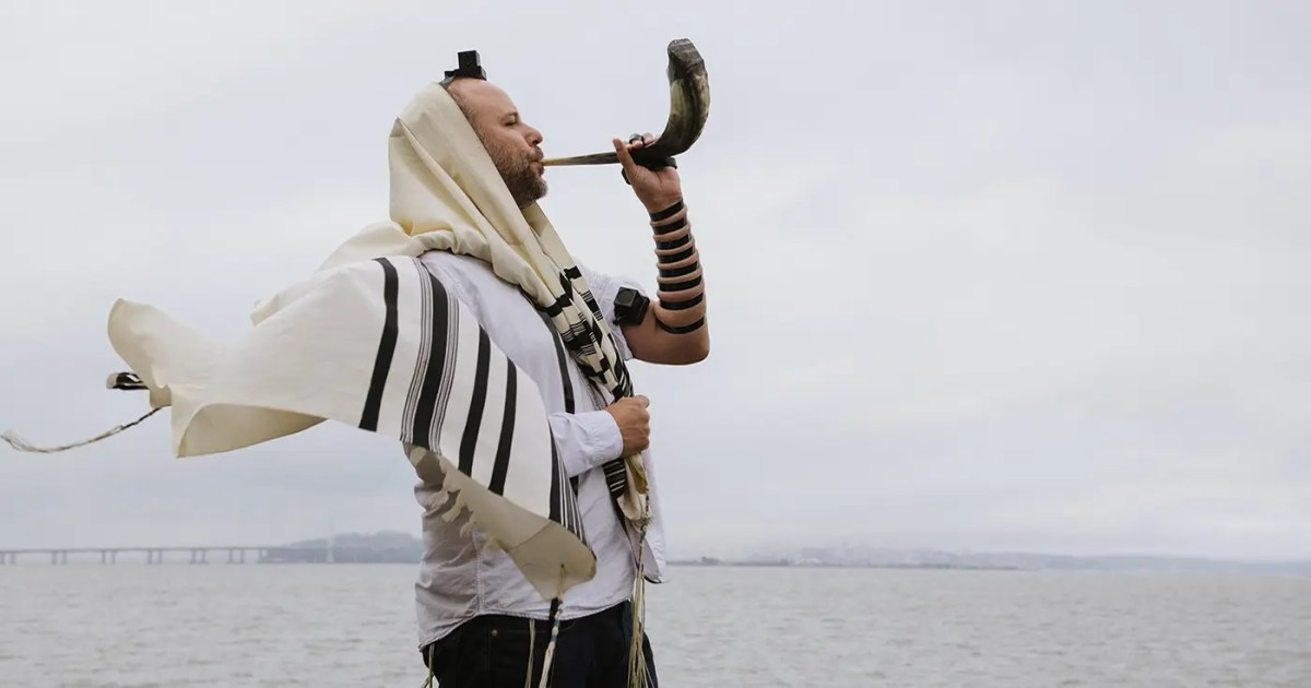 DoubleBlind: Image of Jewish man blowing a shofar in front of lake. In this article, DoubleBlind explores how Rabbi Zac Kamenetz is using psilocybin and psychedelics to reignite Judaism.