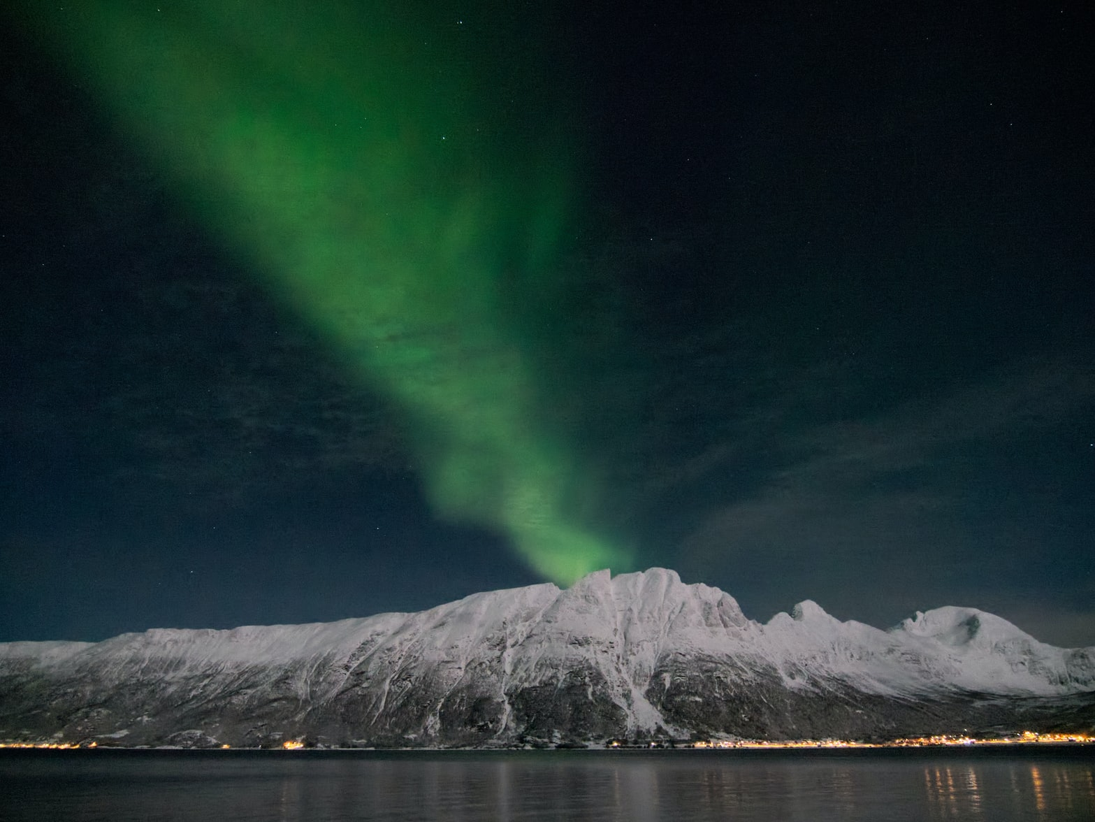An arctic aurora borealis over the snowy mountains