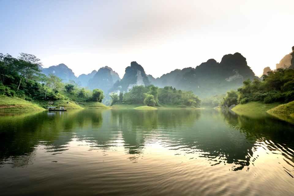 boat on calm lake reflecting limestone mountains at sunset