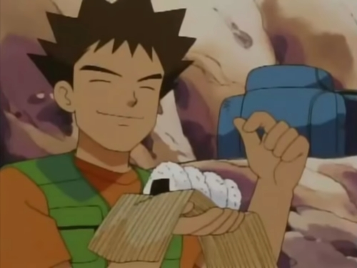 Brock holding rice balls from the anime series Pokemon