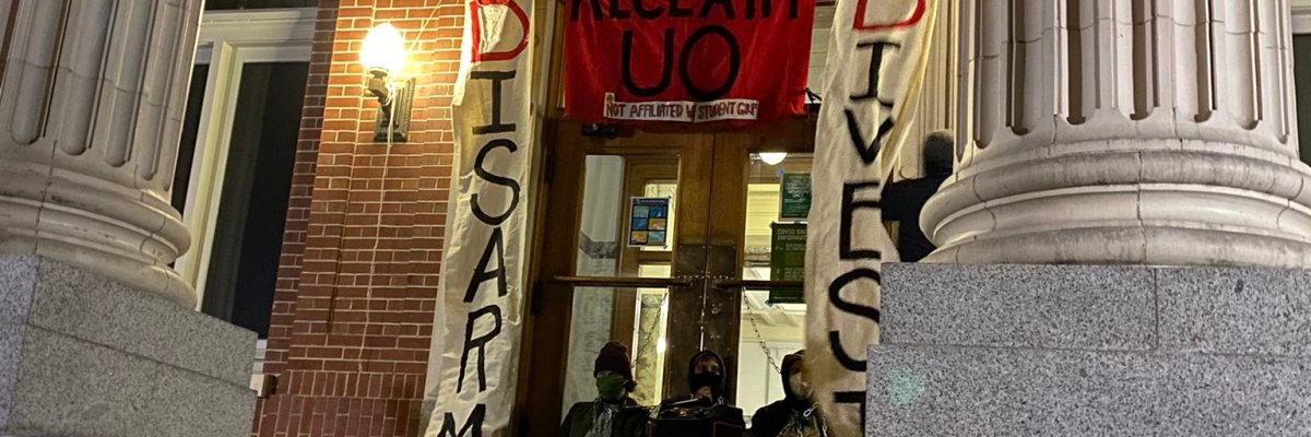 Banners that were unfurled in front of Johnson Hall that read Disarm, Divest and Democratize around a larger banner that reads Reclaim UO