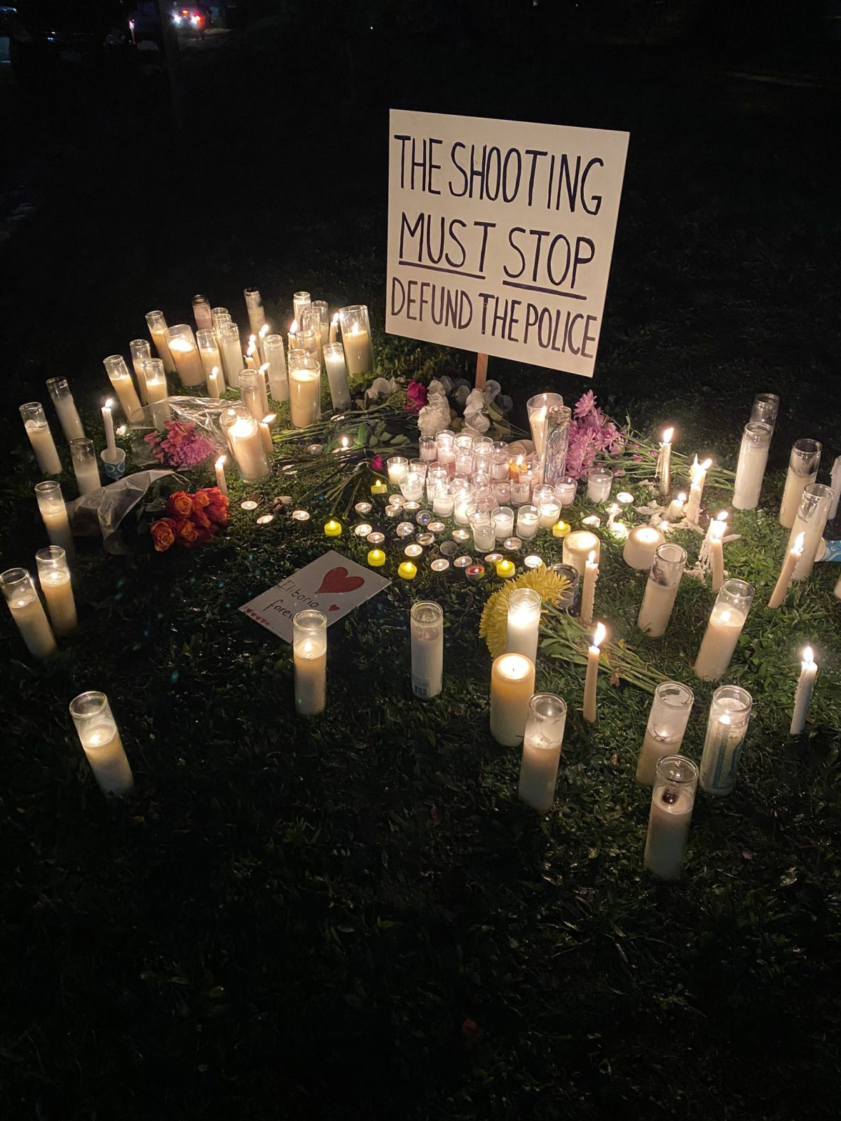 "Night time photo of dozens of candles and flowers laid in front of a sign that reads ""The Shooting Must Stop, Defund The Police"""
