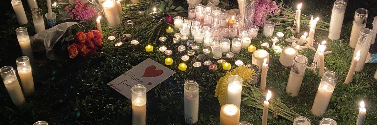"""Night time photo of dozens of candles and flowers laid in front of a sign that reads """"The Shooting Must Stop, Defund The Police"""""""