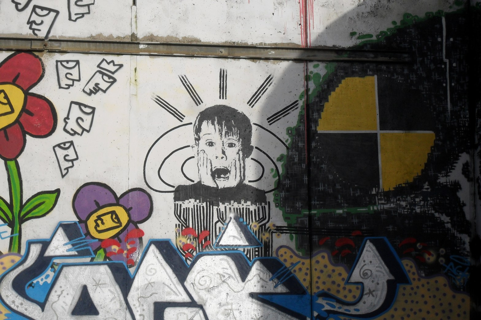 A photo of a wall depicting traditional looking graffiti. in the center is a spray-painted image of Macaulay culkin in the role of Kevin McCallister, doing the iconic hands on face yelling manuever.