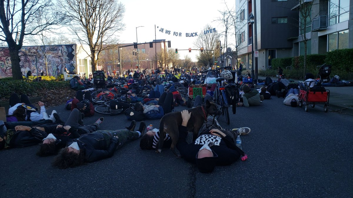 "Photograph of dozens of people laying down in the middle of a Portland street. In the foregrand is a man wearing a surgical mask and holding a skateboard. In the background is a banner that says ""Jews for Black Lives."""