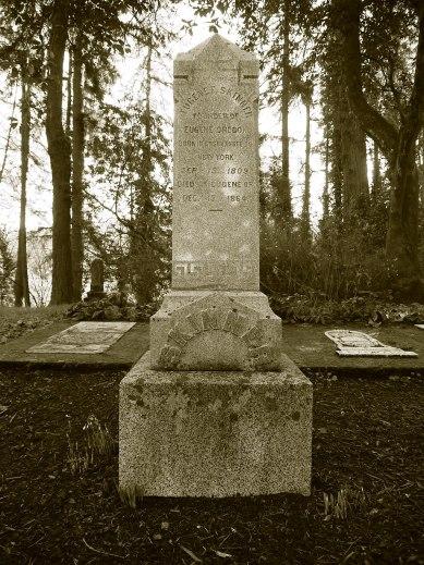 "Photograph of a headstone in the Eugene Masonic Cemetery. The carvings on the headstone read ""Eugene F. Skinner, founder of Eugene, Oregon. Born in Essex, New York on September 15, 1809. Died in Eugene, Oregon December 15, 1864."""
