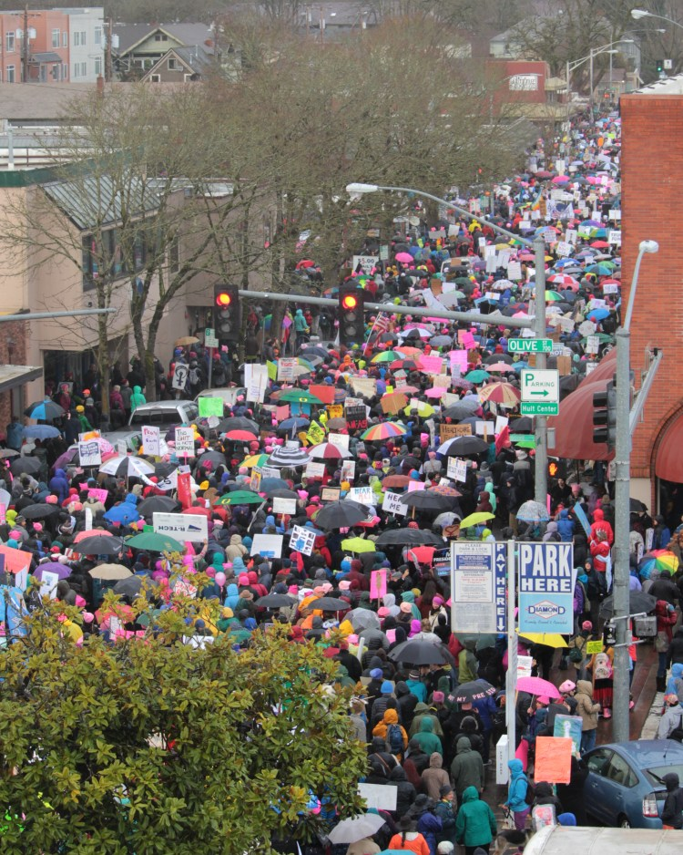 Photograph of hundreds of people filling Eighth Avenue during the first Women's March in downtown Eugene. There are all kinds of signs in the air, but they're too blurry to read out what they say. There is a tree blocking the bottom left quarter of the photo.