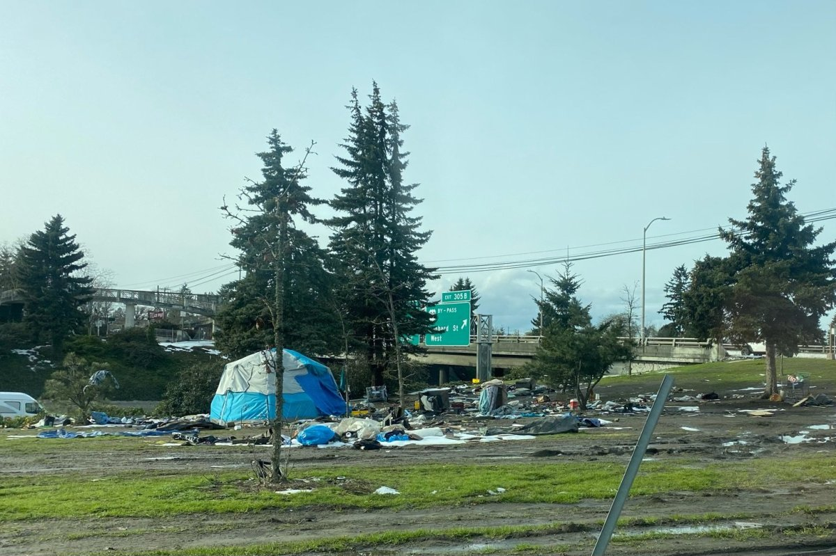A tent set up in the middle of a grassy field near a freeway in Portland, Oregon. There's still snow on the ground, and various trash and garbage surrounds the tent.