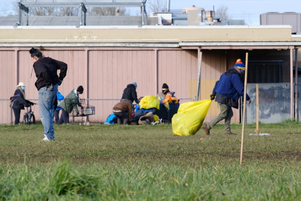 Two people are in the foreground cleaning up trash and putting them into yellow trash bags, while in the background there are four people gathering even more trash and putting them into shopping carts and more trash bags.