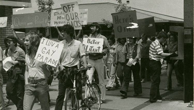 "Black and grey photograph of University of Oregon students marching in a gay pride parade in 1977. A man in the foreground is walking his bicycle, and people around him are holding signs with slogans like ""I love a gay parade"" and ""Better blatant"" and ""Queer and proud"""