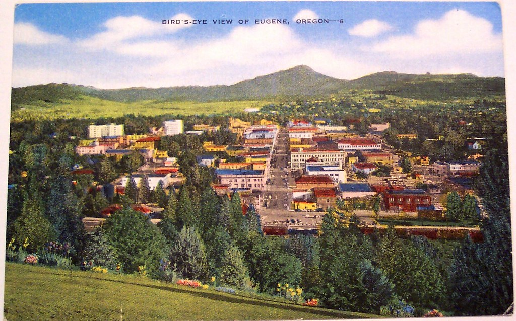 Photo of a postcard with a stylized landscape of Eugene, Oregon with Spencer Butte in the background. It is lush and green and the sky is dotted with white clouds.