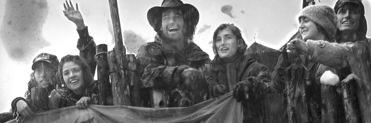 Protests gathered behind a barricade on a forest road during the Warner Creek Occupation, near Oakridge Oregon. The protesters are all scruffy and dirty-looking, and the man in the middle is wearing what appears to be a large cowboy hate