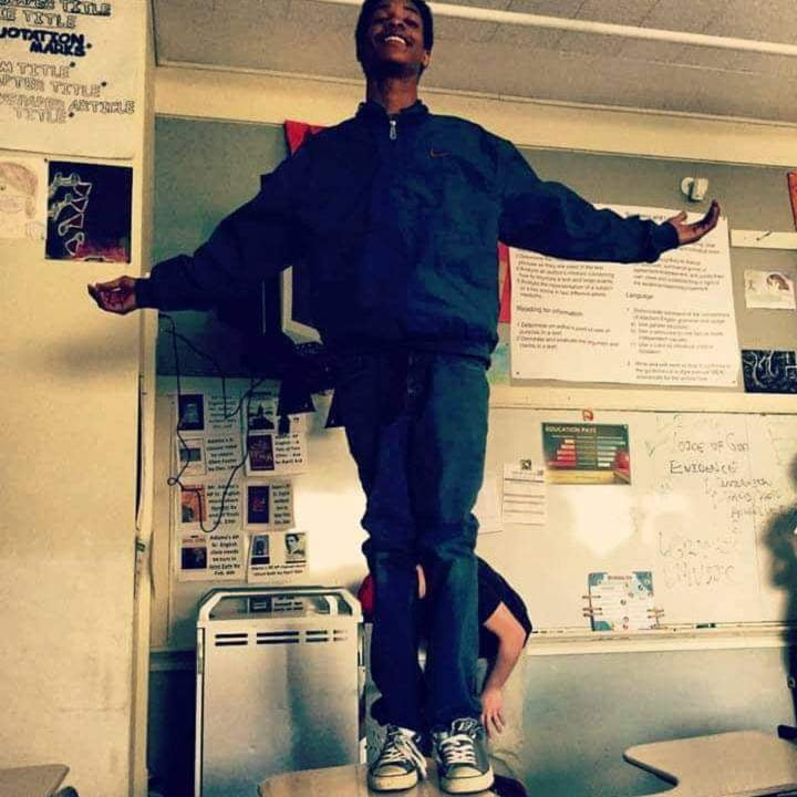 Jermelle Joseph Madison Jr is pictured standing on a desk with his arms outstretched to the side. He is smiling and dressed in blue jeans and a blue windbreaker.