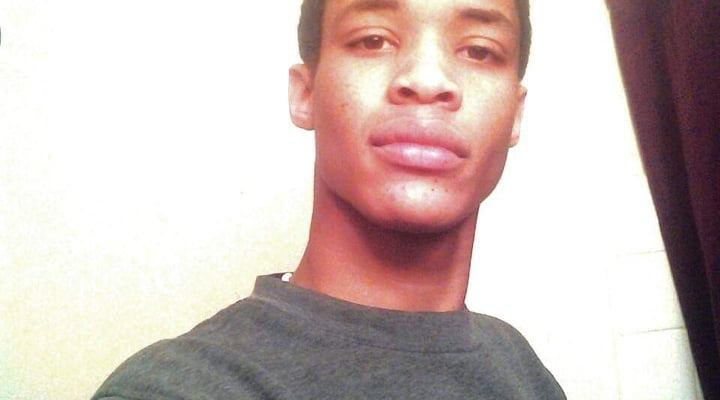 A selfie of Jermelle Madison, Junior. He is wearing a gray long-sleeve shirt and has his hand placed over his chest. He's smirking.