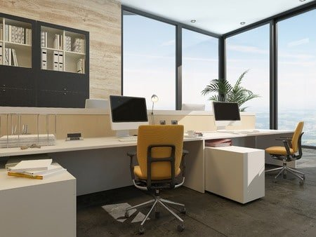 36672925 - spacious work environment in a modern office with work stations at a long table overlooked by a large glass window with views of the sky