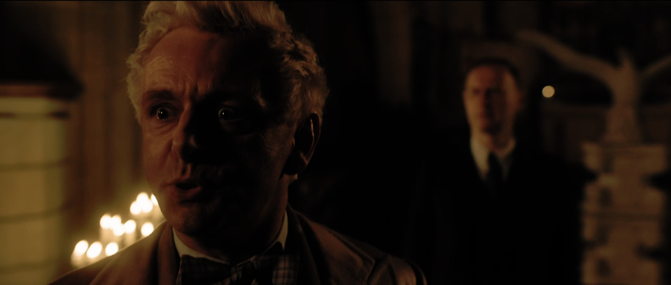 Close-up of Aziraphale (Sheen) angrily asking Crowley (Tennant) what he is doing disrupting Aziraphale's clandestine meeting.