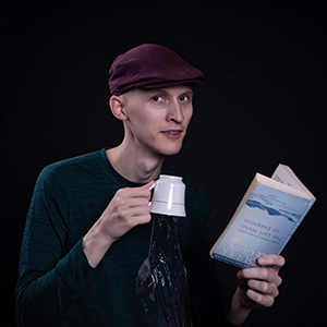 Author Vincent Scott, holding a cup of tea and a book both upside down.