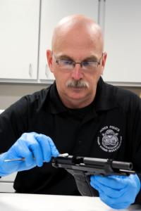 Det. Simpkiss processes a firearm for evidence.