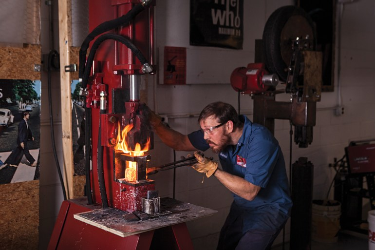 Brant & Cochran metalsmith Gabriel McNeill shapes an ax head for the company's new line.