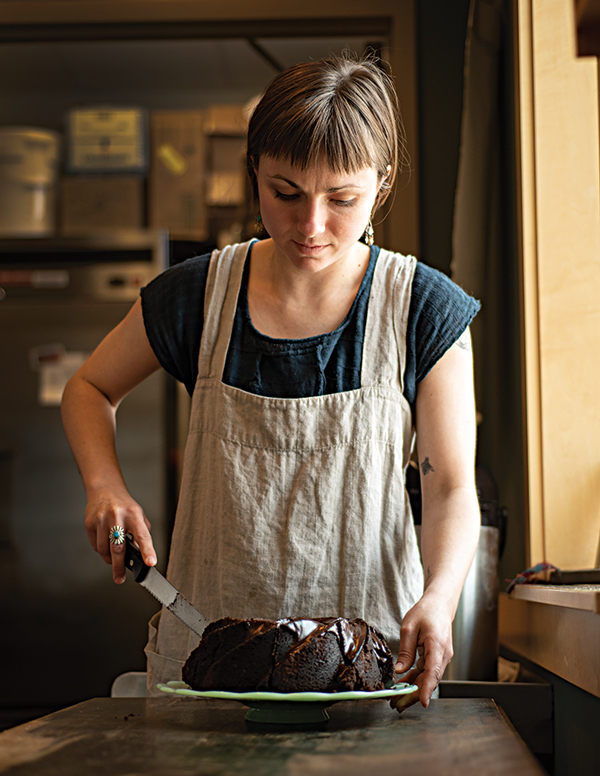 co-owner Erin Dominguez slicing into a velvety chocolate cake