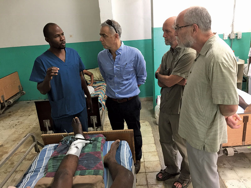 A resident at Justinien University Hospital reviews a case with Konbit Sante staff and physician volunteers.