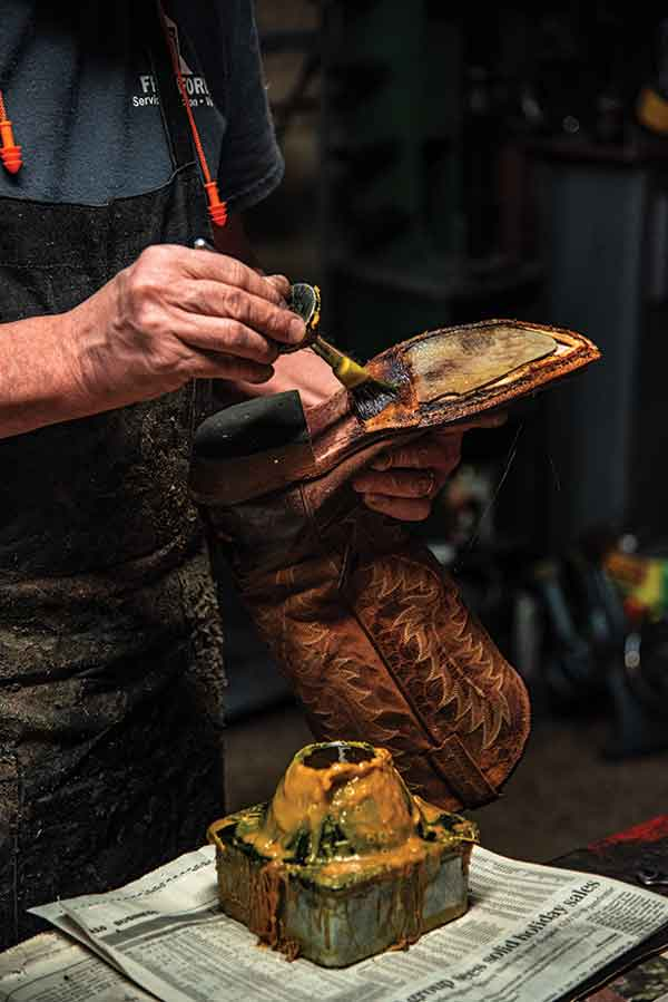 cobbler applying glue for a new sole