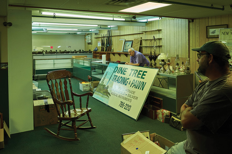 Marcel Morin behind the bar of the now closed Pine Tree Trading pawn shop